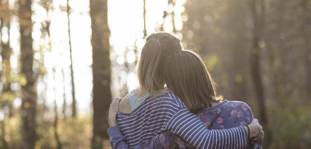 Caregiver Relationships / Myasthenia Gravis News / An image of two women standing in the forest. One has her arm around the other's shoulders.